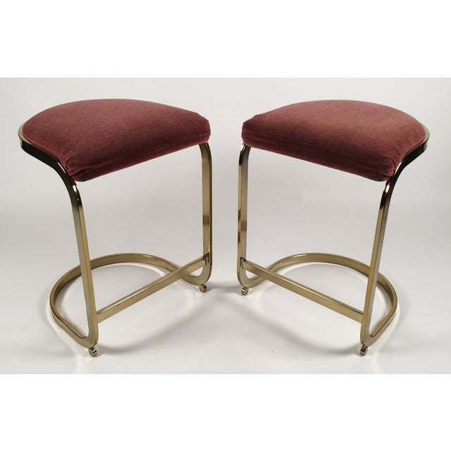 "A pair of mid-century brass cantilevered stools in Milo Baughman style with original mauve fabric. Marked ""Permafab by..."
