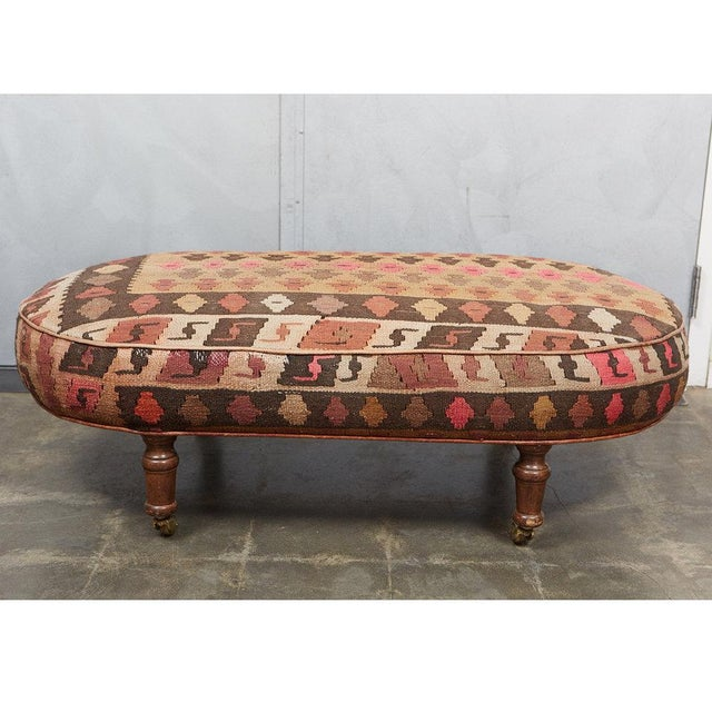 This interesting oval ottoman was custom made in England in the 1980's. It has turned wood feet on casters and wheels. It...