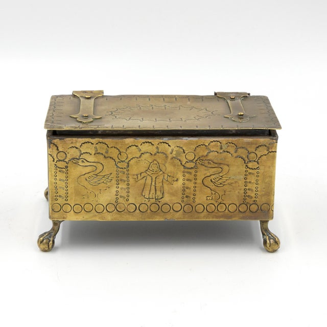 A pair of brass Dutch style table top cigarette or tobacco boxes, each resting on claw feet, engraved decorations of geese...