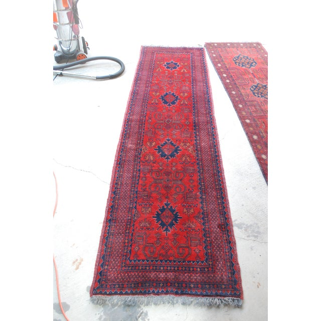 A bohemian low-pile wool runner in rust, reds and blue accents. Hand-knotted wool. Symmetrical design, great vintage...