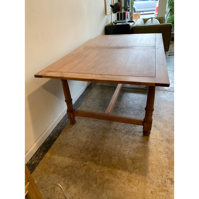 Beautiful antique French farm table with turned legs and foot rest. Made in the early 20th century.