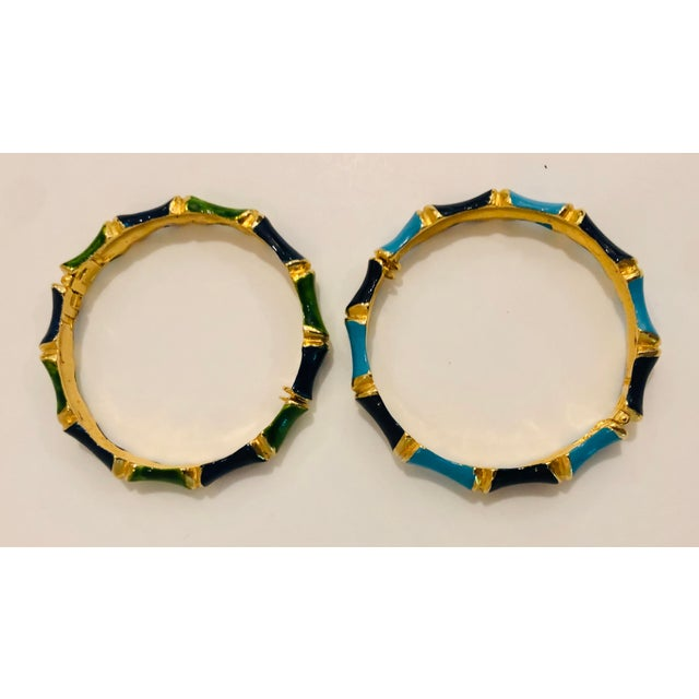 Vibrantly colored in greens, blues and gold, thin enameled bamboo shaped bracelets, circa 1980s. Both open with a clasp....