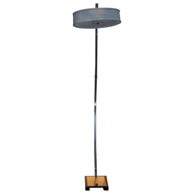 Tall, freestanding, arcing floor lamp. Shallow rectangular base with black border. Comes with one white drum shade. In-lne...