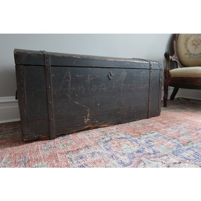 A large wood steamer trunk with original paint circa 19th c. Even to be seen is what is left of someone's name displayed...