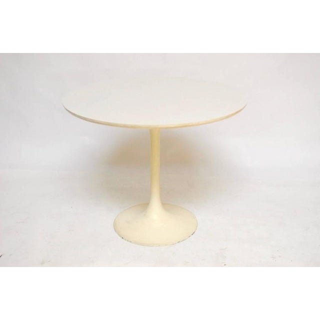 Mid-Century tulip dining table featuring a round laminate white top and an aluminum base with a light cream finish. The...