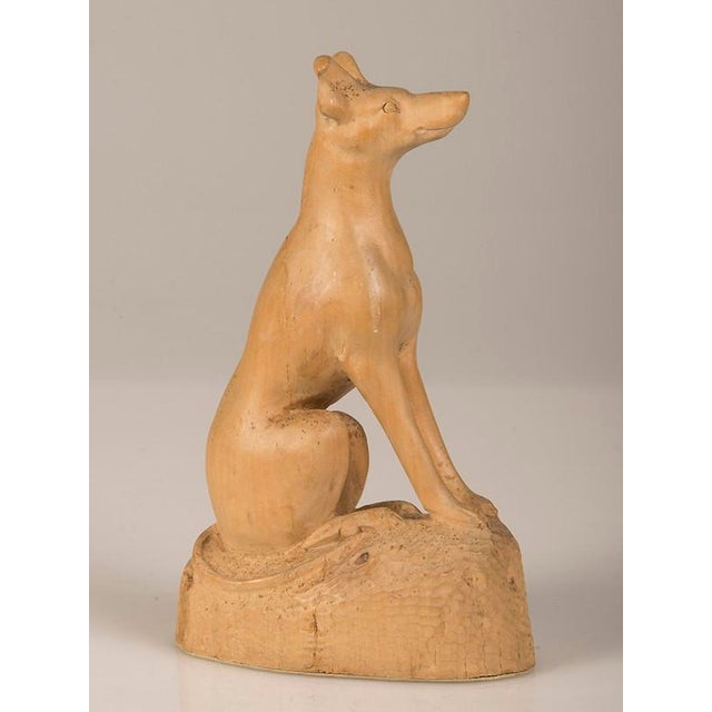 A charming naïve hand-made sculpture of a dog carved from a single piece of timber from England c. 1890. Please notice the...