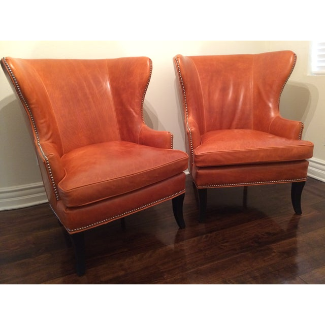 Pair of leather wing back chairs by Williams Sonoma Home. Custom ordered in a special deep burnt orange leather with...