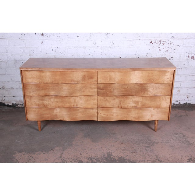 Offering a rare and exceptional mid-century modern wave front long dresser designed by Edmond Spence. The dresser features...