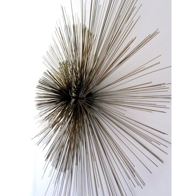 Fantastic wall sculpture comprised of 3 (three) tiers of brass spokes. Center protrudes 10 (ten) inches from wall.