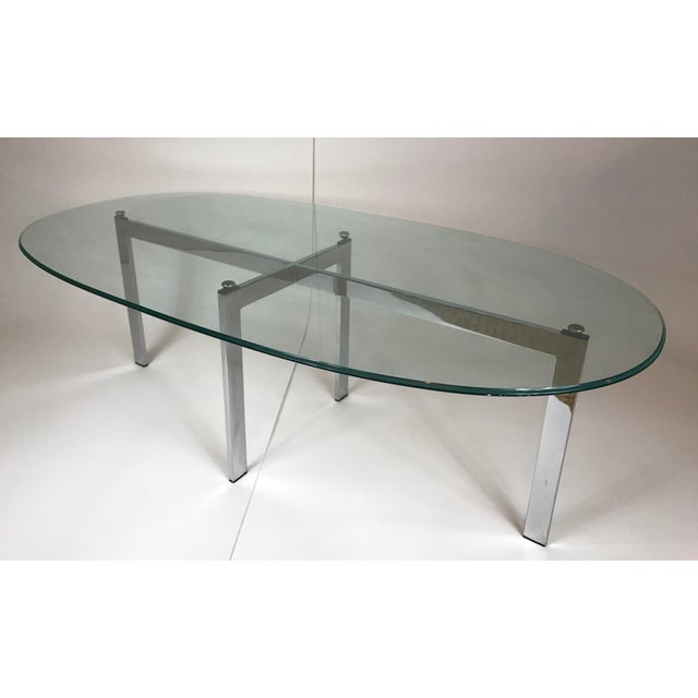 "1970's chrome base cocktail table with thick oval beveled glass top. Base measures 42""W x 15""D x 15.5""H and glass measures..."