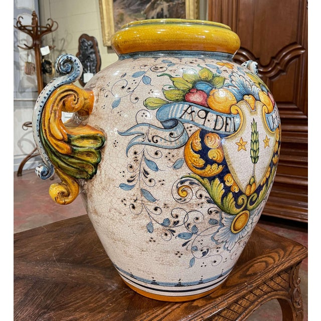 Created in Italy circa 1960 and round in shape, the antique planter is decorated with elegant acanthus leaf side handles....