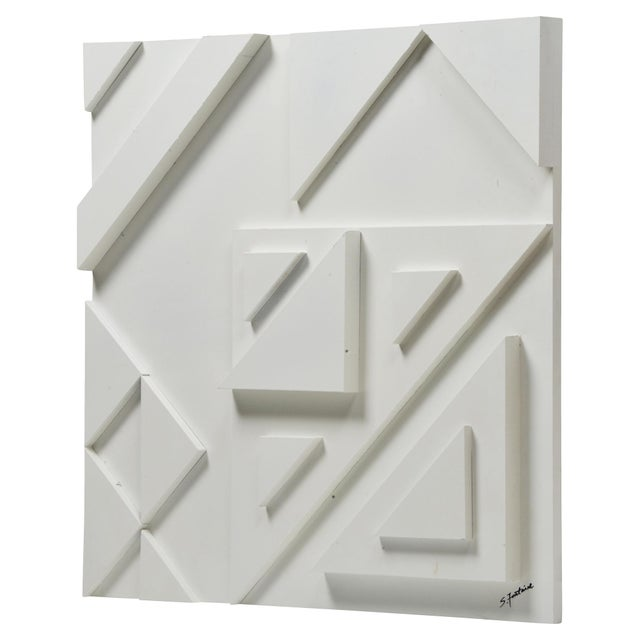 High-relief stripes and assorted stacked triangles create the stark composition of this three-dimensional geometric wall...