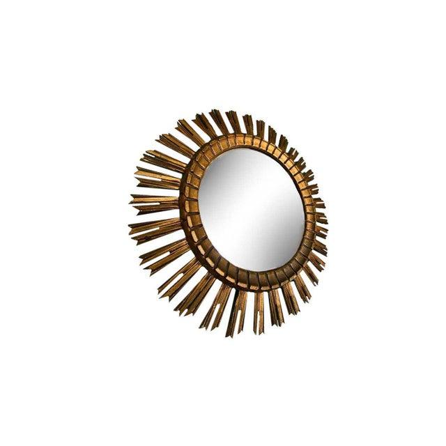 "A 24"" diameter, 19th century sunburst mirror. Gilt with red rub through."