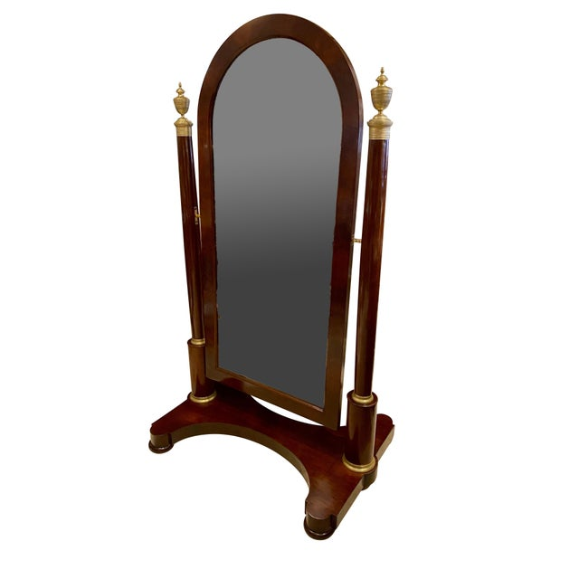 With an arched mirror plate set in a conforming wood frame that swings, all attached to a pair of cylindrical posts each...