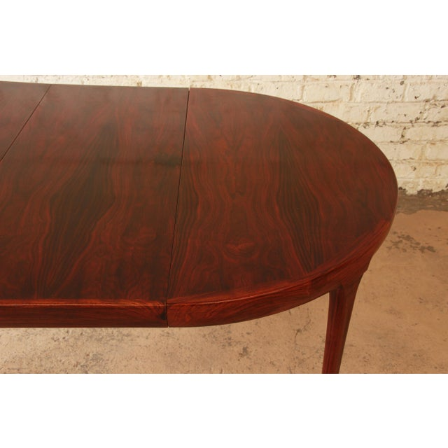 Offering a rare and stunning Mid-Century Danish Modern rosewood extension dining table designed by Ib Kofod Larsen for...