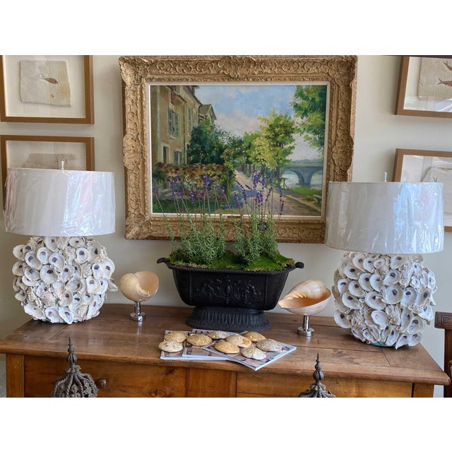 A pair of oyster shell table lamps will beacon you to the sea. Beautifully arranged organic shells and custom linen shades.