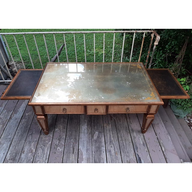Item offered is a Theodore Alexander Eglomise Collection Glass and Wood Large Coffee Table. It has 2 long wide drawers and...