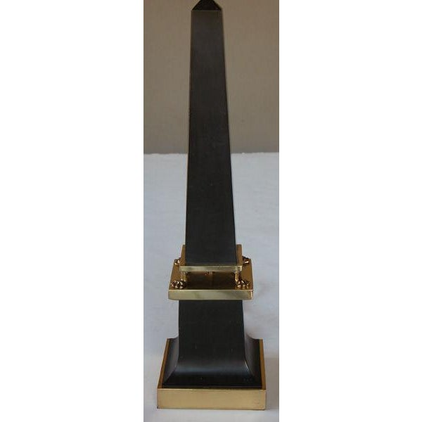 A sleek French 1940's black painted tole obelisk-form lamp with brass mounts; the graduated obelisk-form body raised on 4...