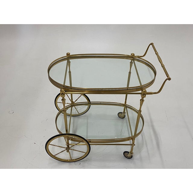 LaBarge elegant solid brass vintage bar cart having two oval glass tiers with gallery surrounds. Measures: 30 H to handle...