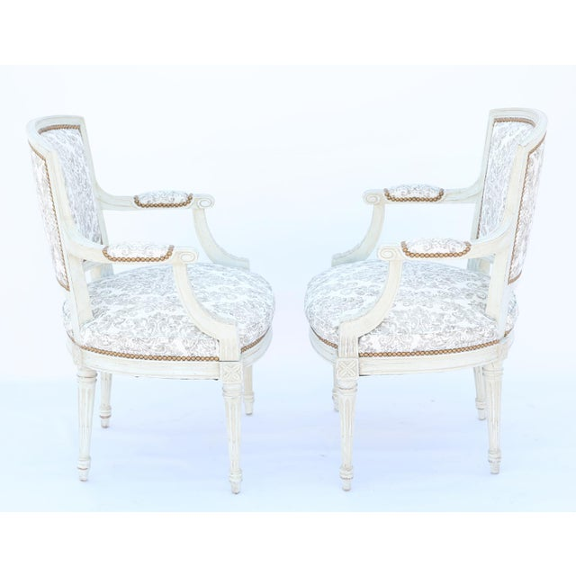 Pair of Louis XVI armchairs, each having a painted, channelled frame, showing natural wear to finish, padded, shield-...