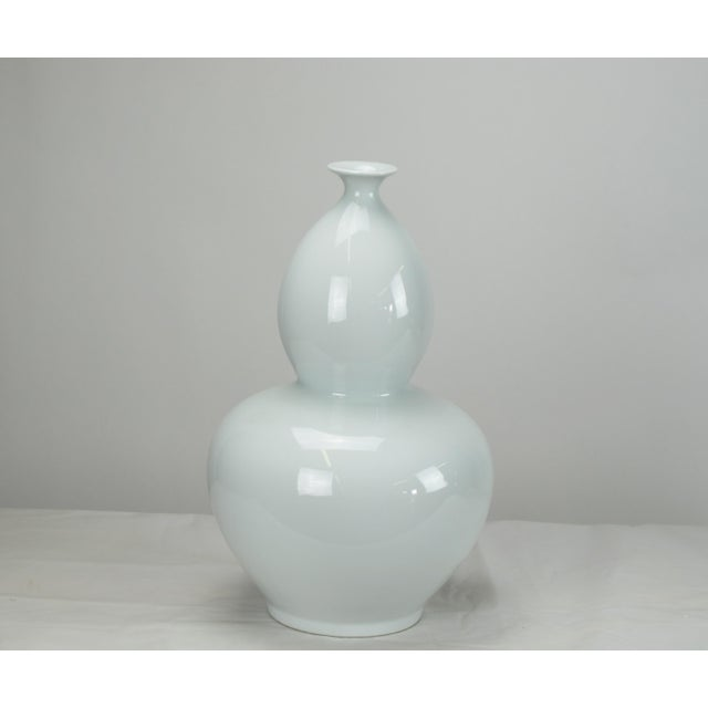 A symbol of immortality and happy life, this bottle gourd vase with glossy white finish has smooth curving streamline...