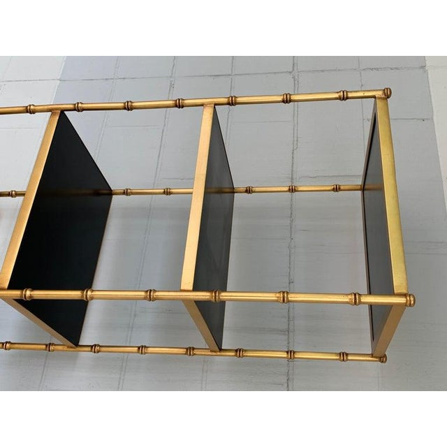 """Gilt metal and lacquered faux bamboo étagère, fitted with six black lacquered 14"""" x 13"""" black lacquered shelves."""