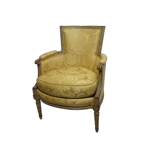 Carved and painted Louis XV style bergère chair, having yellow silk damask upholstery and a down cushion. Upholstery is in...