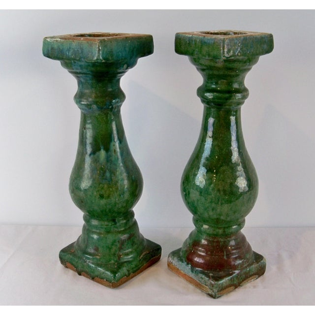 A pair of unusual antique Chinese balustrade posts. There are subtle details both in the design and color of each post....