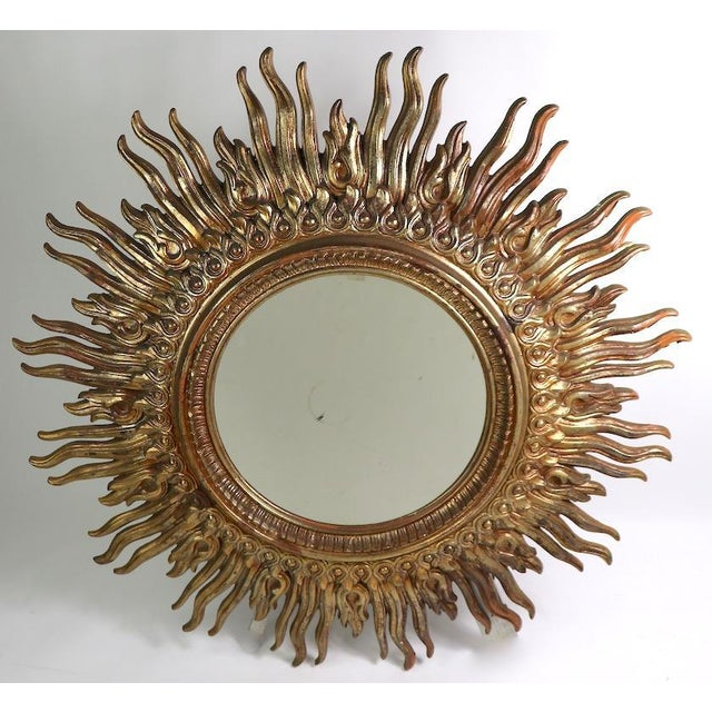 Large circular sunburst frame mirror with cast resin faux gilt frame. The frame has radiating rays surrounding the...
