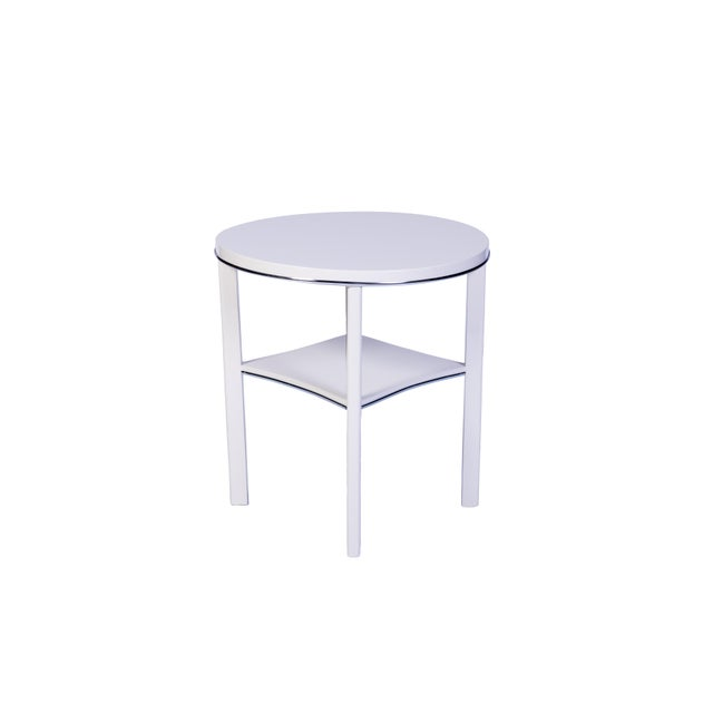 This chic Art Deco side table features a simple design with chrome line detailing finished in a luscious high gloss white...