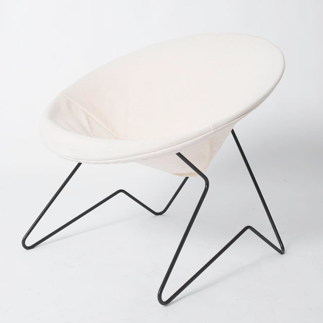 """A wrought iron patio hoop chair with cantilevered hairpin legs in a """"Crow's foot"""" shape. The sling is made of cotton..."""