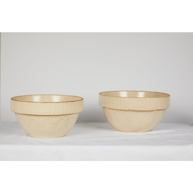 Early 20th Century American Art Deco earthenware or yellow ware pottery nesting bowl set. The mixing bowls' pattern is...