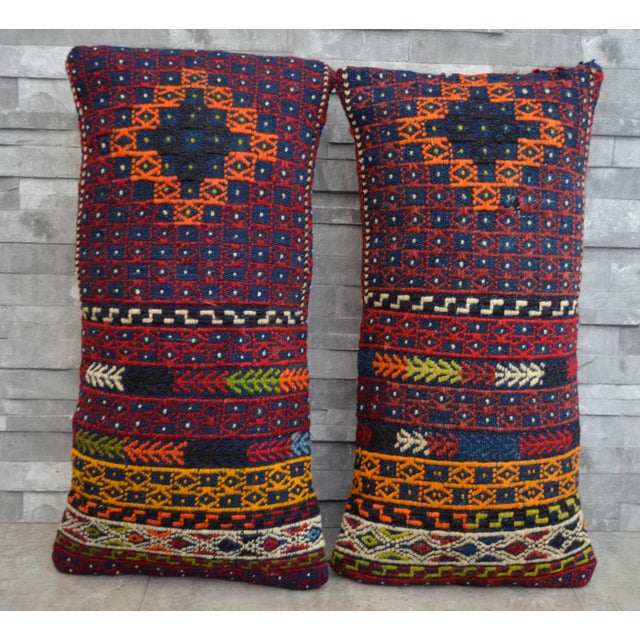 Offered a pair of Turkish kilim lumbar pillow covers made from a vintage hand woven wool on wool kilim rug. The back side...