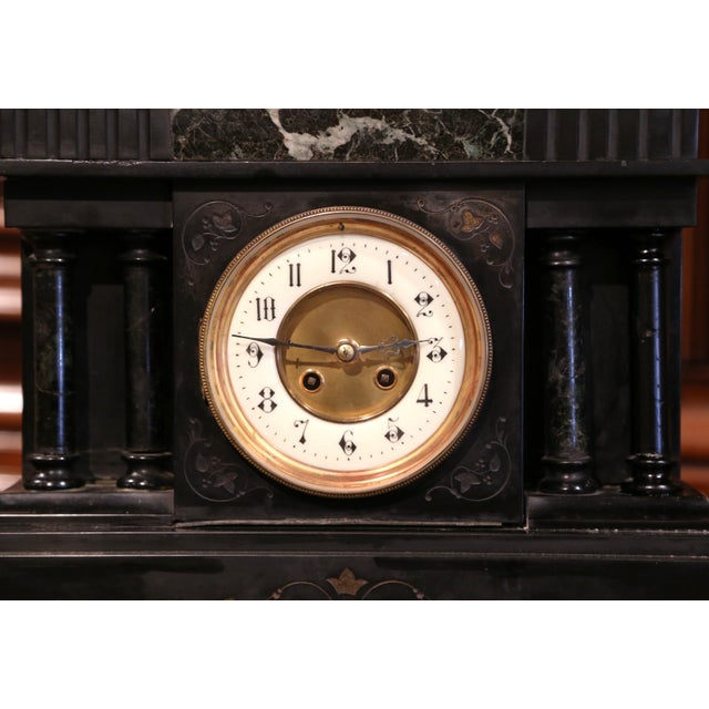 This elegant, antique clock was carved in Paris, circa 1880. The mantel clock is made of a carved black and green marble...