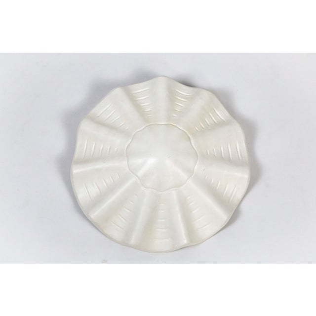 A white, lacquered plaster pendant in an undulating shell shape, with scalloped edges and imprinted lines accentuating the...