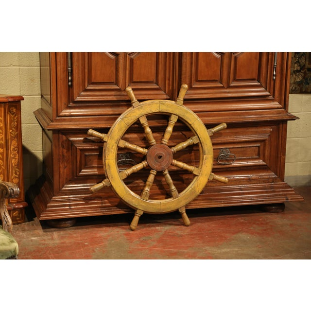This antique wooden ship wheel was carved in France, circa 1880. The traditional, fruit wood nautical object has its...