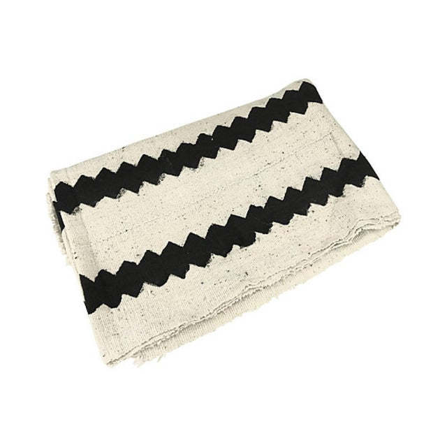 Handcrafted throw made from African handloomed cotton mud cloth strips sewn together and colored with natural dyes. Age...