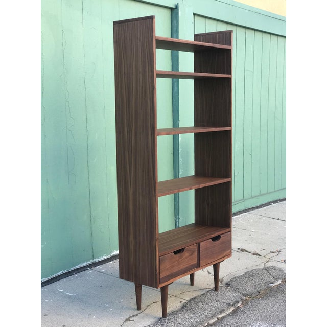 Custom Mid Century Style Bookcase or étagère made of walnut wood, here in LA California. Pin legs carry the base and give...
