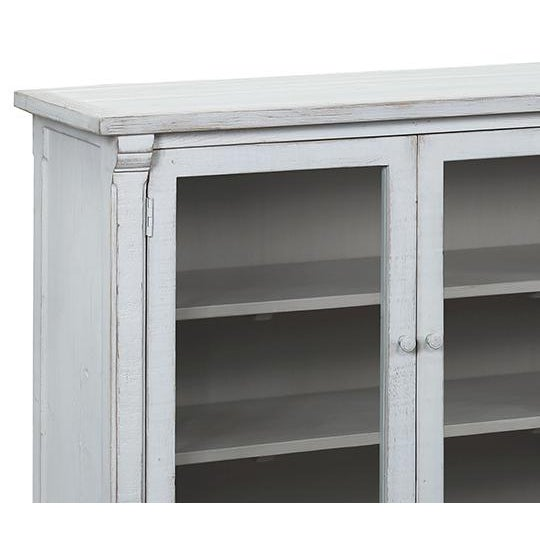 Distressed rustic pale grey painted sideboard with glass panels in doors. Each cabinet section includes two shelves. Each...