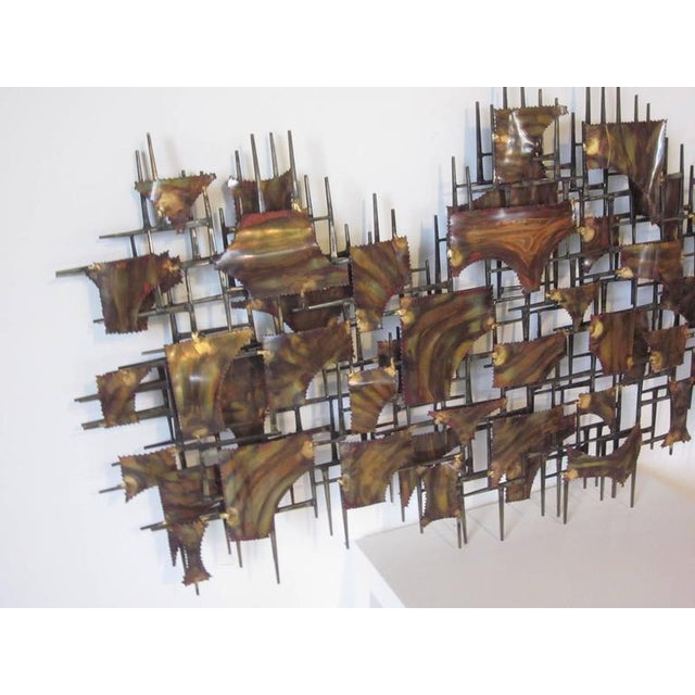 A torch cut, flamed and welded large metal wall sculpture in copper and brass tones contemporary in design with built in...