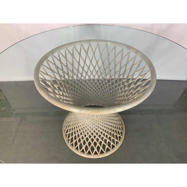 Woven rattan pedestal table features sculptural hourglass shape and round glass top. Very good condition with only minor...