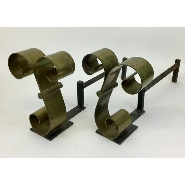 Excellent vintage handmade scroll form andirons in solid brass, with iron backs, attributed to Raymond Subes. These have a...