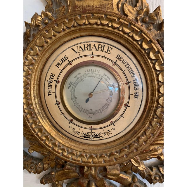 A magnificent antique Louis XVI style giltwood wall barometer and thermometer having a rectangular Celsius thermometer in...