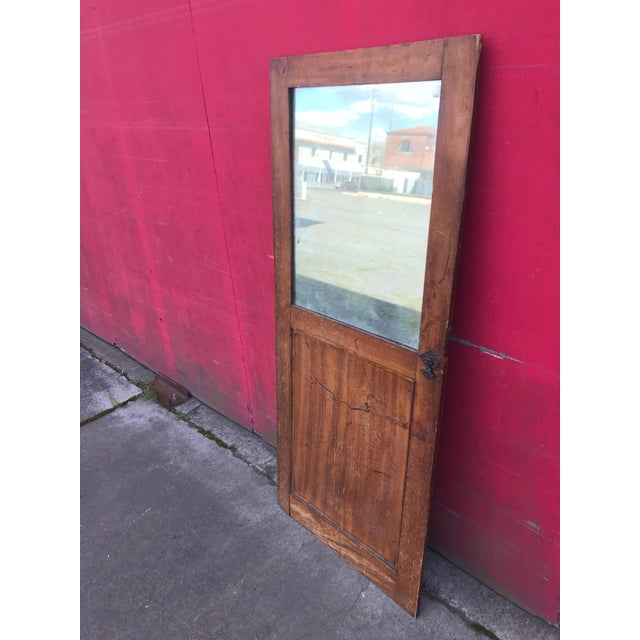 Handsome decorative antique architectural fragment—this wood-paneled door with ornate iron cast iron hardware and original...