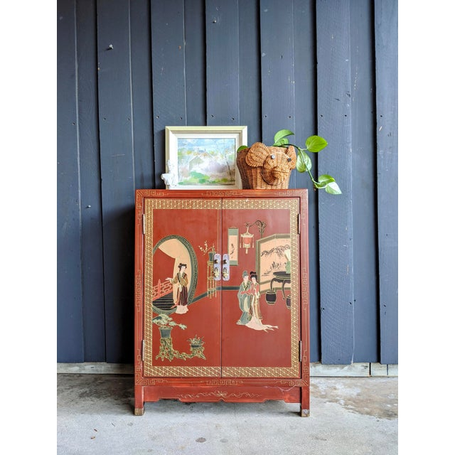 Beautiful cinnabar red, circa 1960s, hand-painted cabinet wit brass wrapped feet and brass hardware. Doors close nicely...