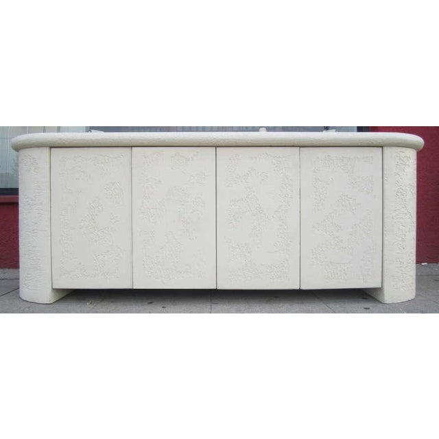 This striking credenza with rounded edges features a faux stone finish in textured plaster surmounted by a white washed...