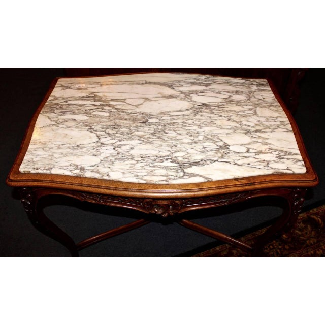This French library table is made in the Louis XV style from walnut. The table is adorned with hand-carved detail and is...