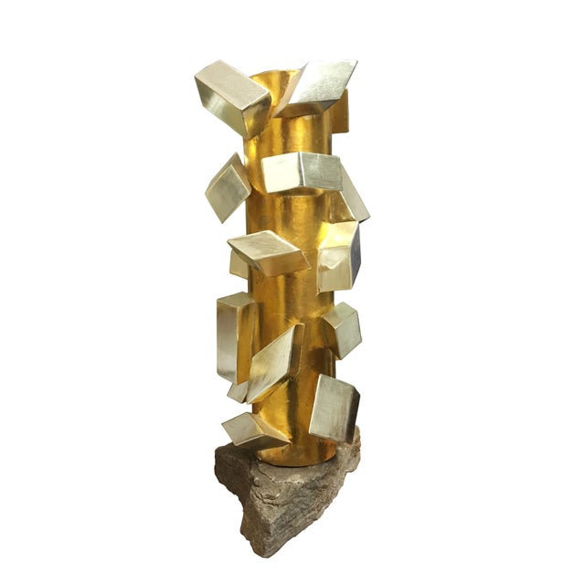 Abstract cubist sculpture juxtaposed by a natural stone base. Cylindrical pillar gilt in 22K gold with a matte finish....