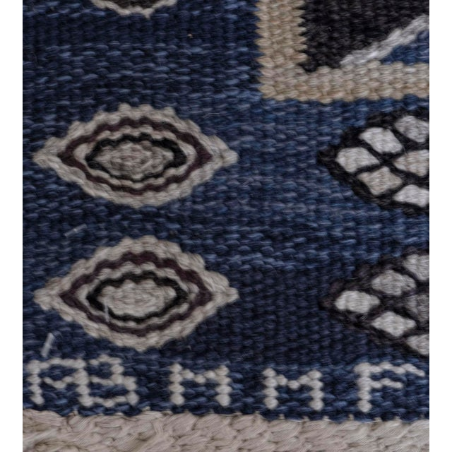 This Mid-Century Swedish rug has a shaded blue field with a central column of linked chocolate brown and dark-brown sharp...