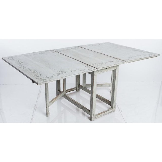 A Gustavian Style painted-wood table with gate legs made in Sweden in the 19th century. The table top retains an original...